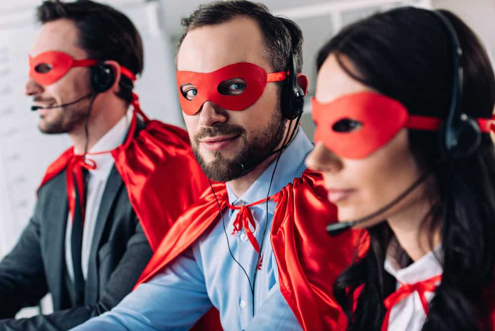 Three call center representatives wearing capes and masks, with the middle one looking at the camera with a mischievous expression.