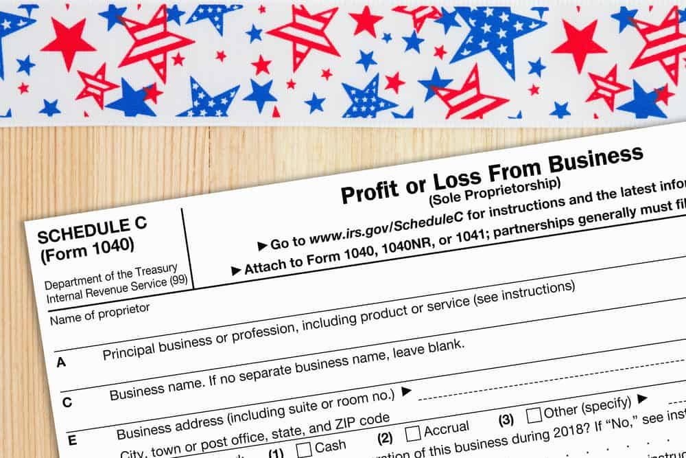 A US Federal tax 1040 schedule C income tax form on a desk with USA banner