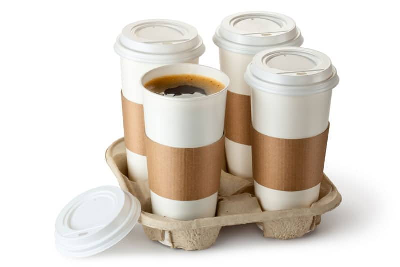 """Picture of a cheap pressed paper cup holder holding four cups of coffee,, with the caption """"We look at the best drink holders that Doordash Uber Eats Grubhub and Postmates contractors can use (and no, this is not one of them)"""""""