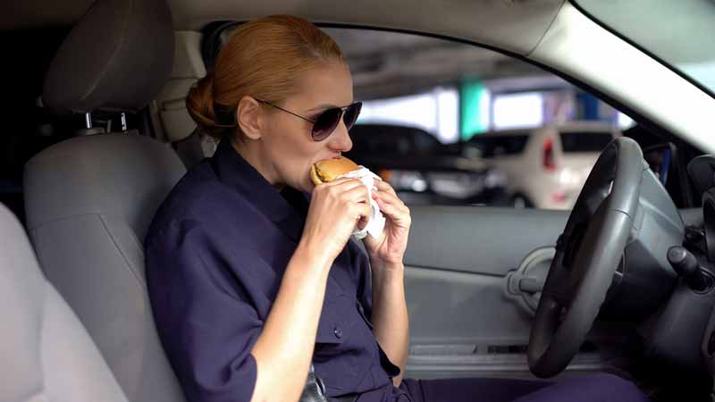 Woman eating a meal lin her car - I ask if she can claim a deduction for this meal as a business expense if she's delivering for Doordash, Grubhub, Uber Eats, Postmates, Instacart?