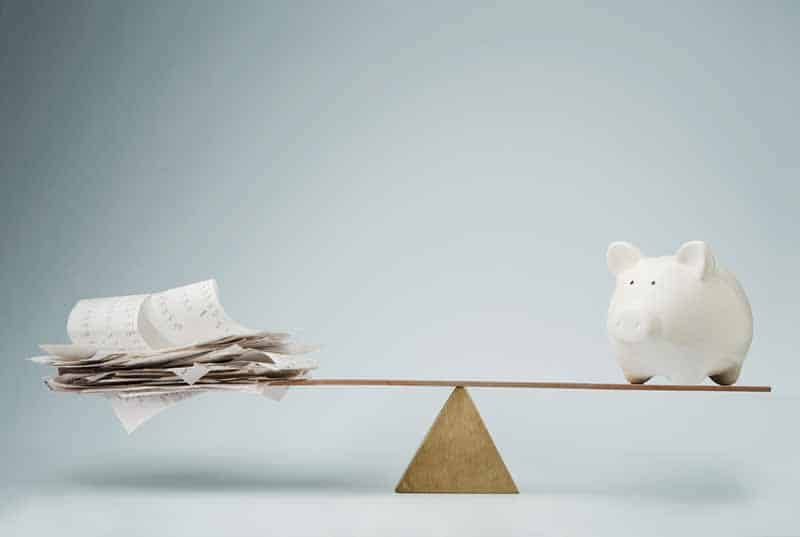 Piggy bank and expenses balancing each other out.