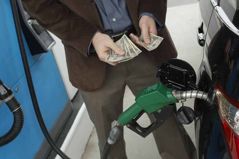 Man holding money counting the actual expense of using car as he buys gas