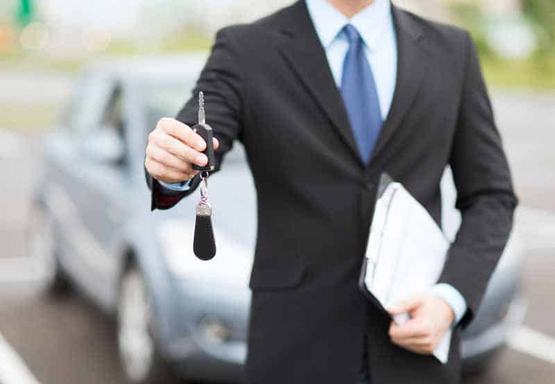 Salesman handing keys to someone who leased and claims the payment under actual expenses