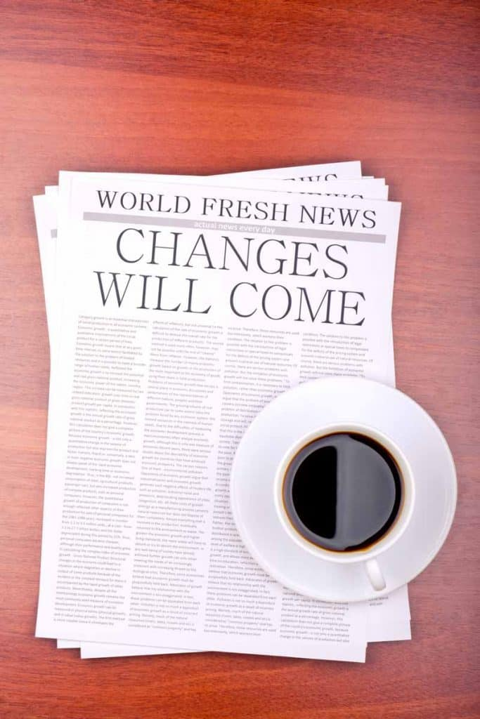 Cup of coffee on top of news article stating Change will come.