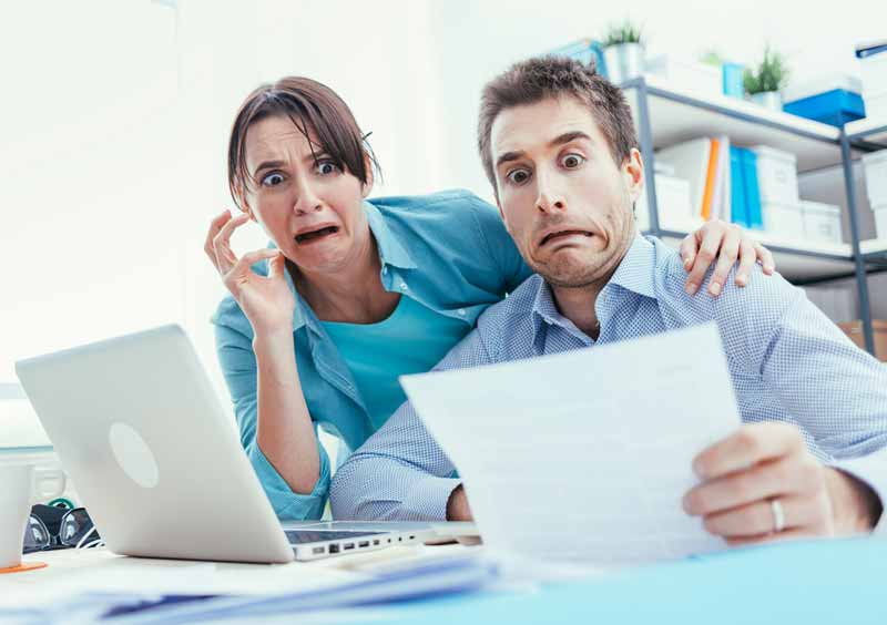 Couple with horrified expression as they look at their tax bill.