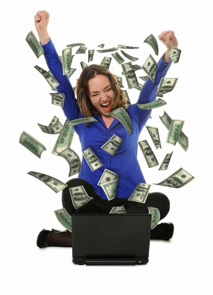 Woman celebrating with money falling at her laptop because of lower taxes