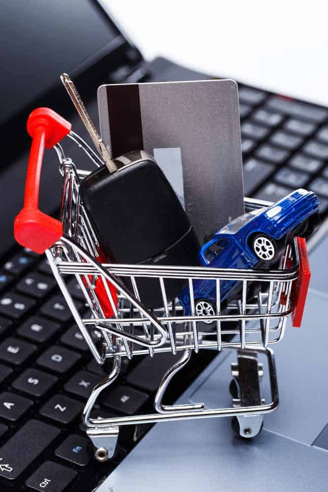 car, credit card and keys in a small shopping cart on a keyboard while someone shops for Doordash car insurance