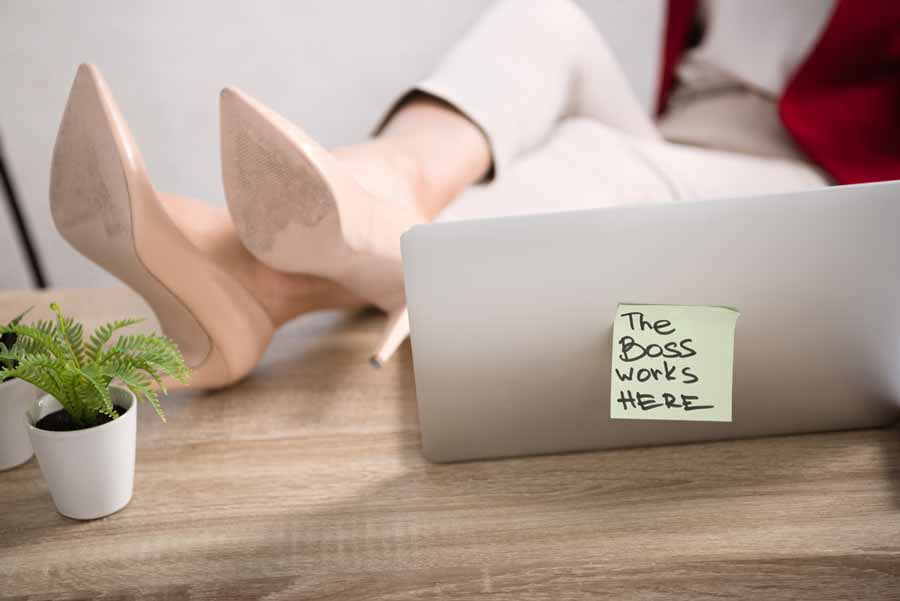 """person relaxing with post-it on their laptop that says """"the boss works here"""""""