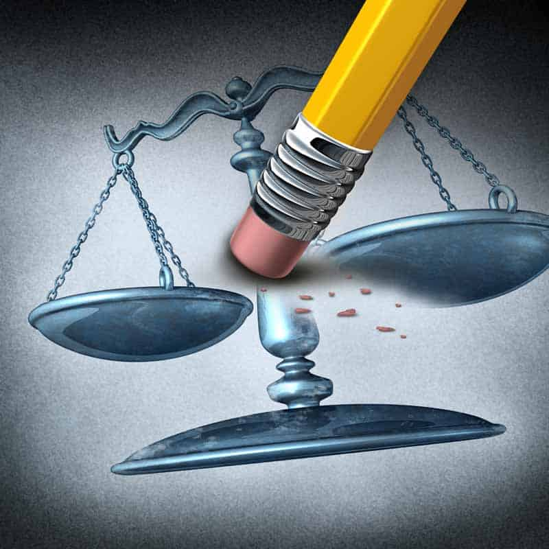 eraser erasing legal scale signifying unjust and unfair practices.