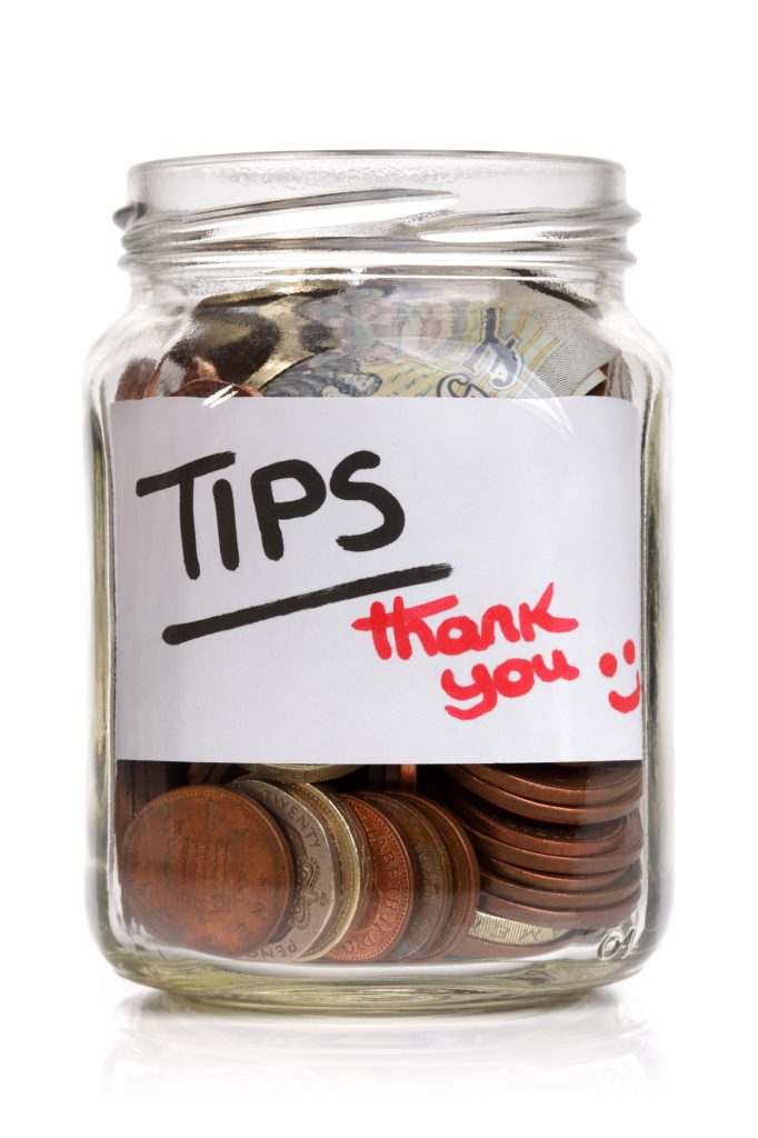 Tip jar with currency and coins representing Grubhub's new tip policy