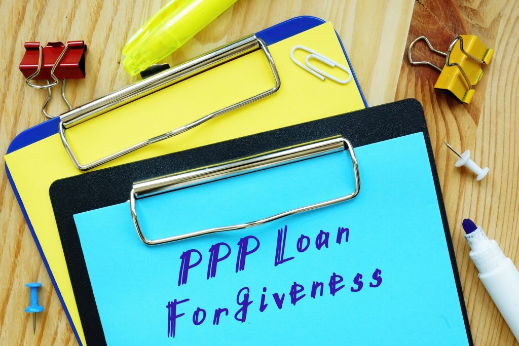 Handwritten text on clipboard with PPP (for Paycheck Protection Program) Loan Forgiveness