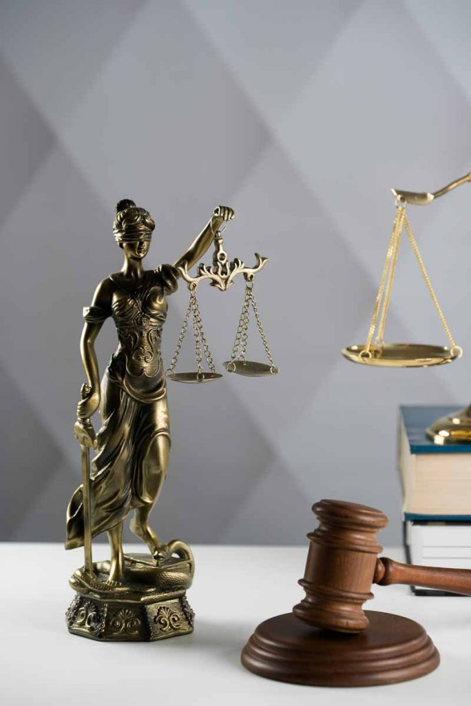 Legal theme related to Doordash arbitration with statue of lady justice, gavel and law books
