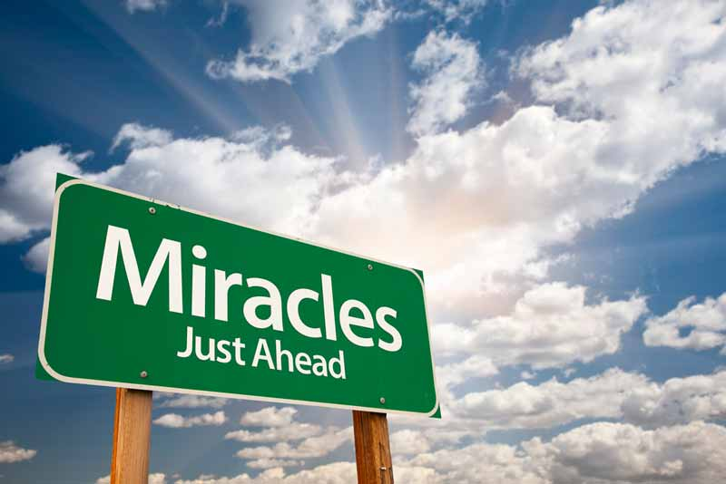 "Sign stating ""Miracles ahead"""