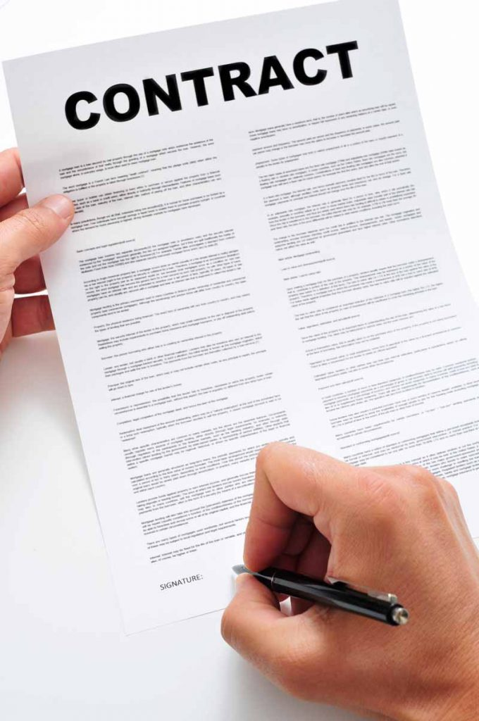 Picture of hand signing an agreement like the doordash independent contractor agreement