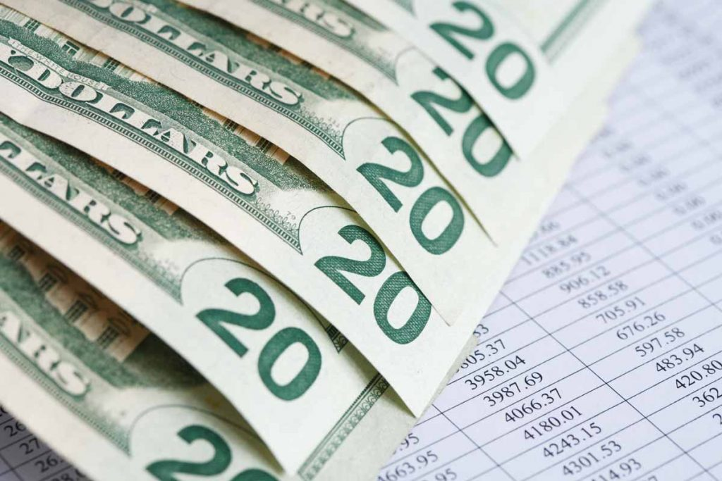 Dollar bills on top of a ledger sheet for bookkeeping
