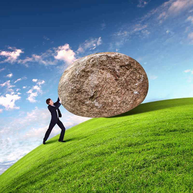 Business man struggling to keep giant rock from rolling down hill and over him