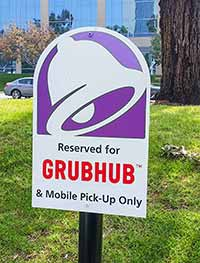 Restaurant sign reserving parking for Grubhub drivers