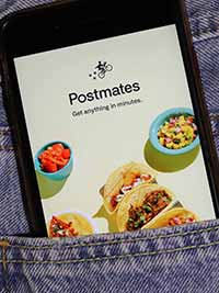 Postmates app on a phone in someone's pocket.