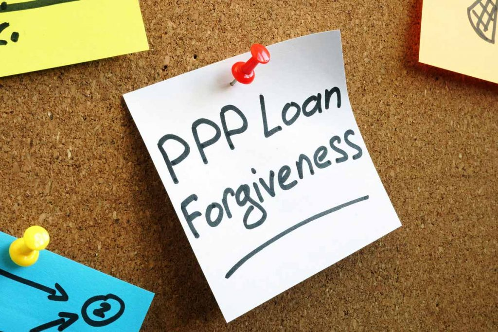 Post it note on a bulletin board with the words PPP Loan Forgiveness
