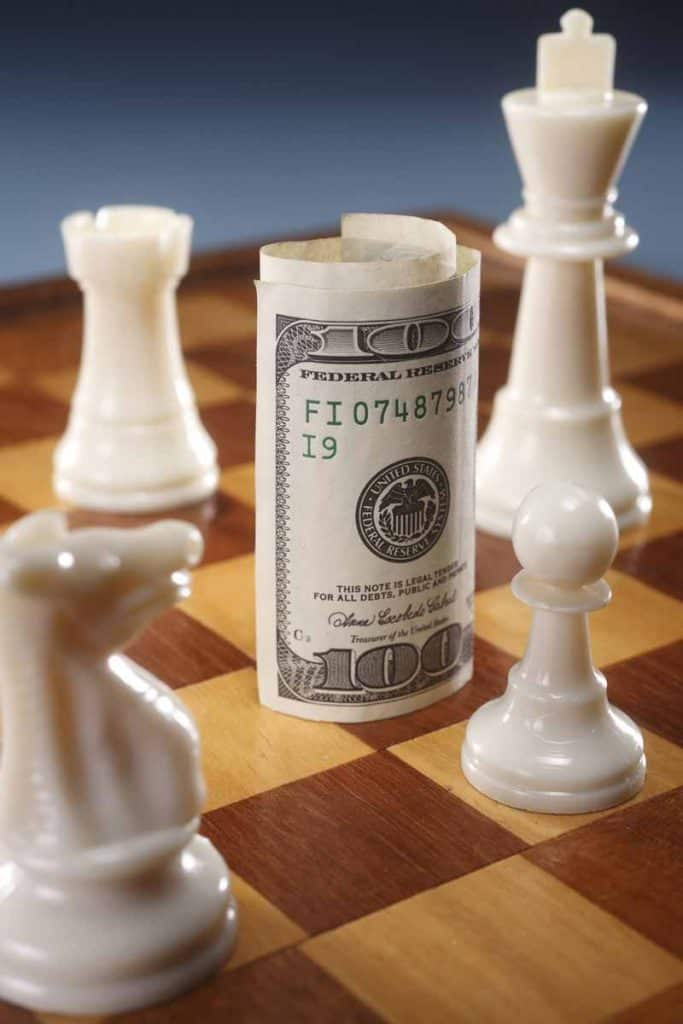 Chess board concept with a $100 bill serving as one of the chess pieces.