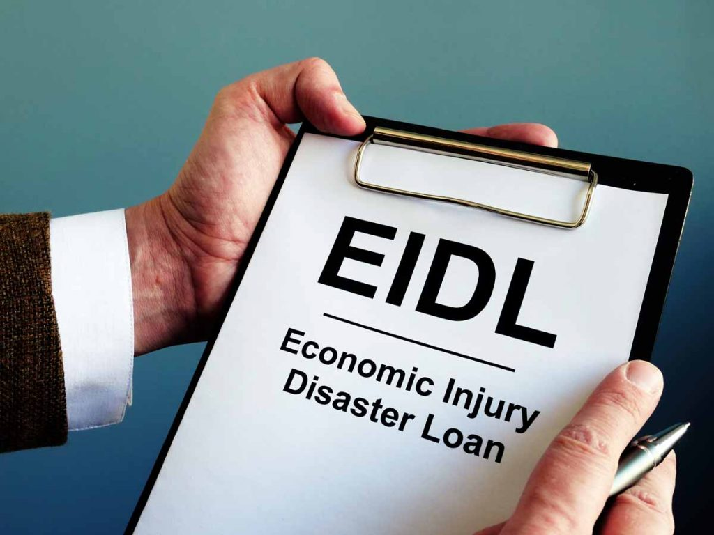 businessman holding pen, clipboard and application for the COVID-19 EIDL Economic Injury Disaster Loan