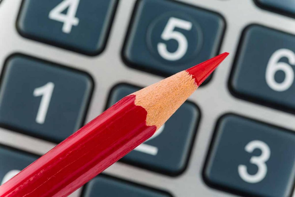 a sharpened red pencil and calculator used to calculate reduction of income for the paycheck protection program