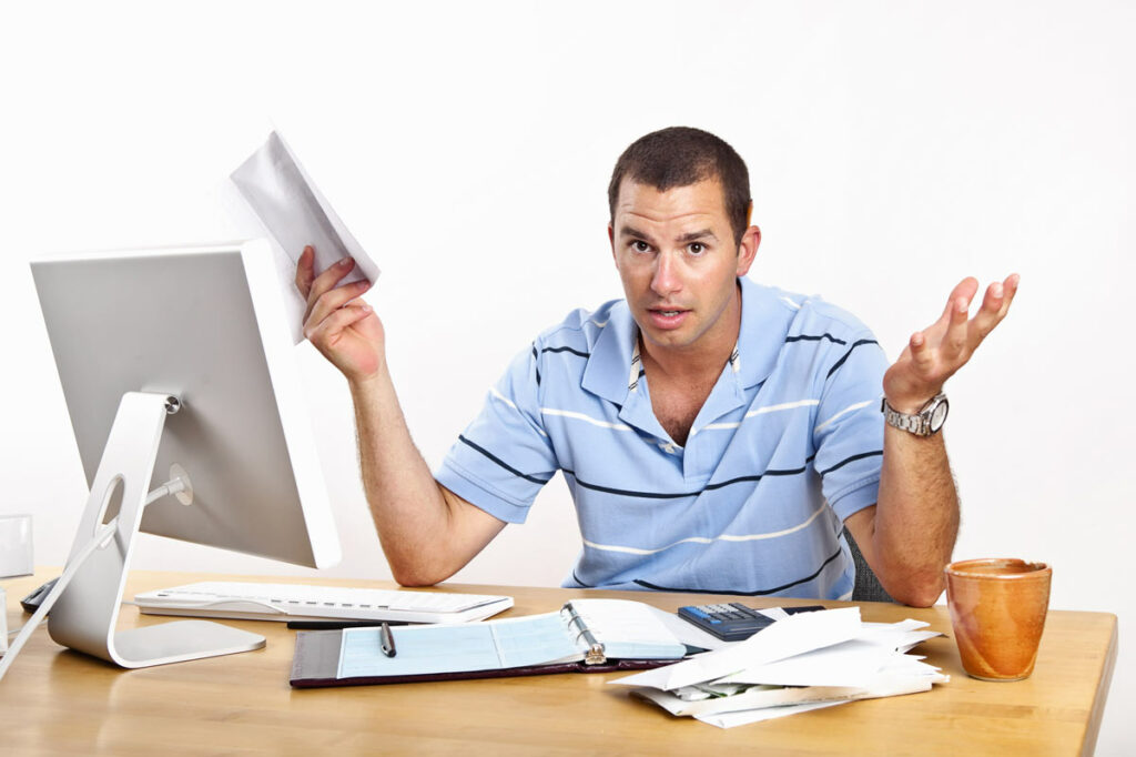 Man at his computer with confused look on his face while holding tax information from Uber.