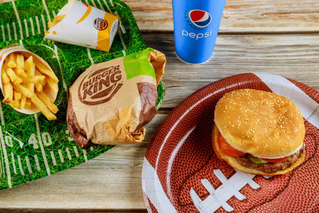 Layout of fast food that was delivered for the Superbowl, with burgers, fries, a drink and football decorations.
