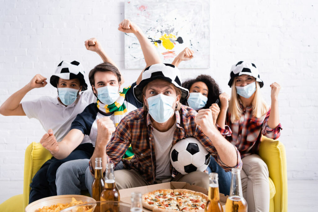 Fans at a home football party with snacks and beer wearing masks.