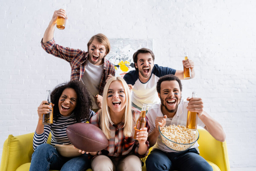 Friends on a couch at home enjoying the Superbowl cheering, drinking beer, eating popcorn