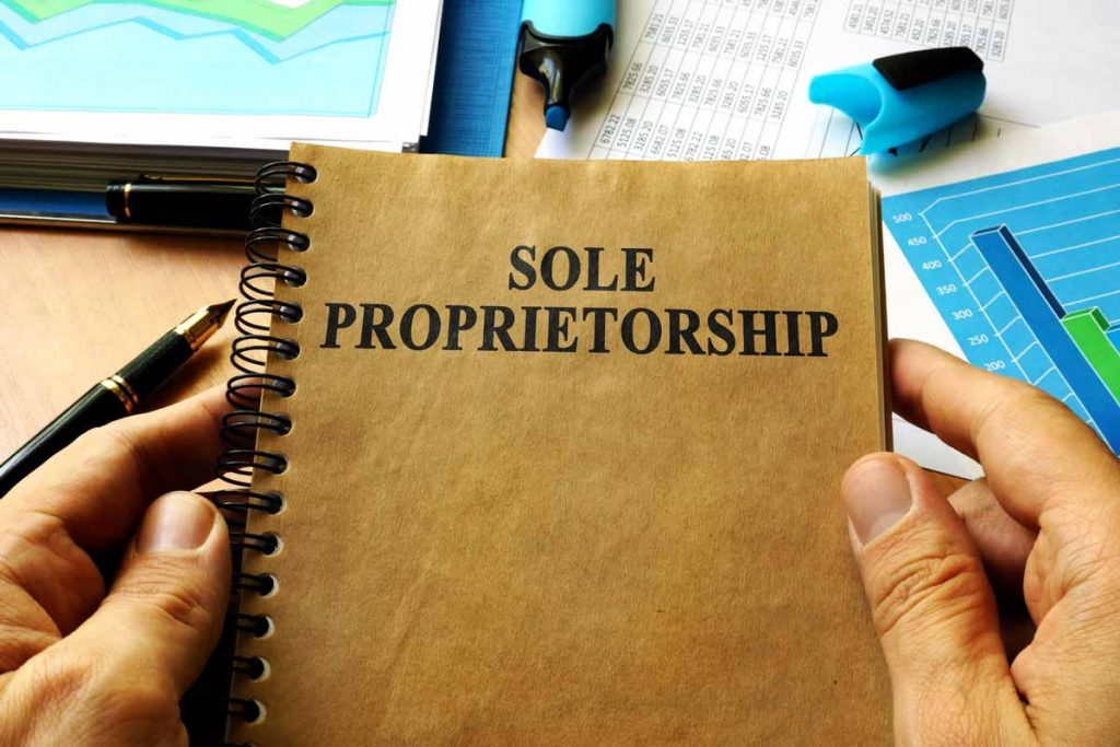 Hands of an independent contractor holding a sprial bound booklet entitled Sole Proprietorship