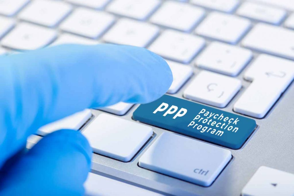 Gloved finger pressing PPP Paycheck Protection Program button on a keyboard