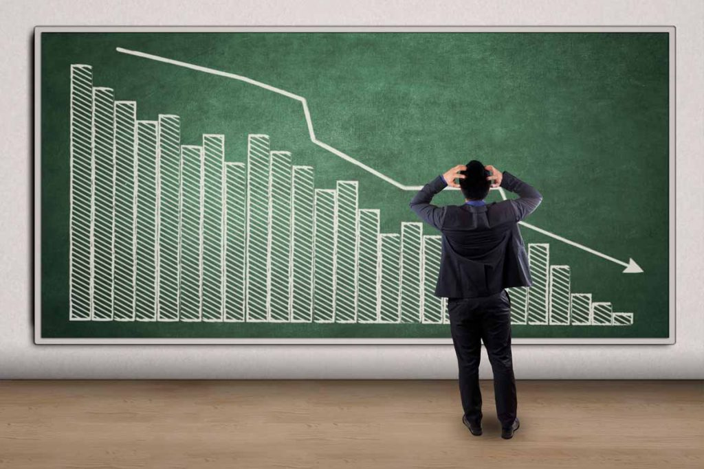 Frustrated business owner standing before large bar graph showing a reduction in income