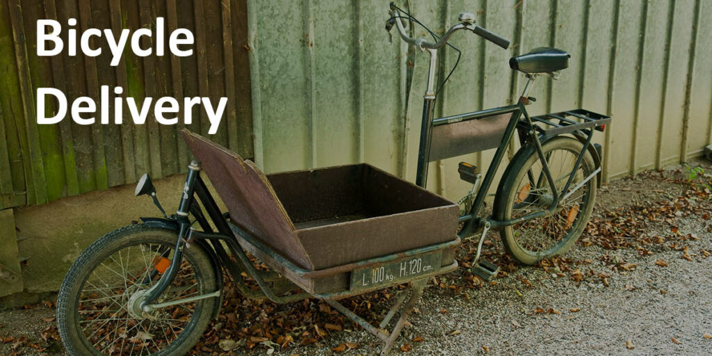 """Bicycle Delivery"" label over picture of older cargo bike against a metal wall."