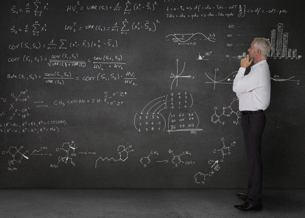 Man studying complex equations on a chalkboard.