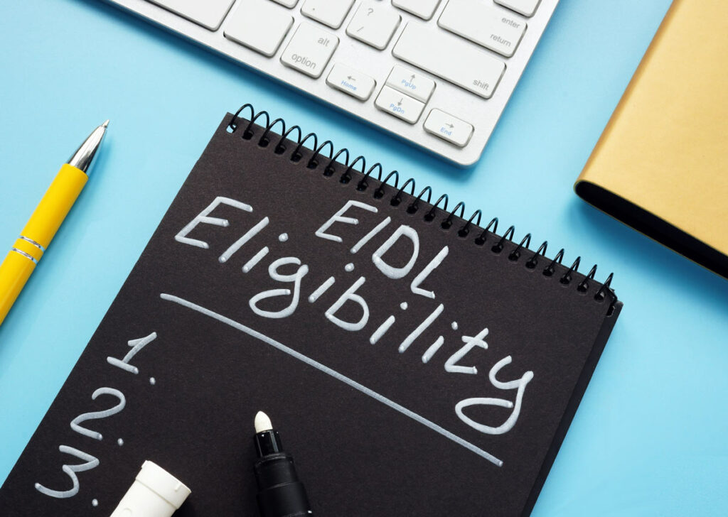 Black notebook on blue desktop with white marker lettering reading EIDL Eligibility, with 3 numbered spaces.