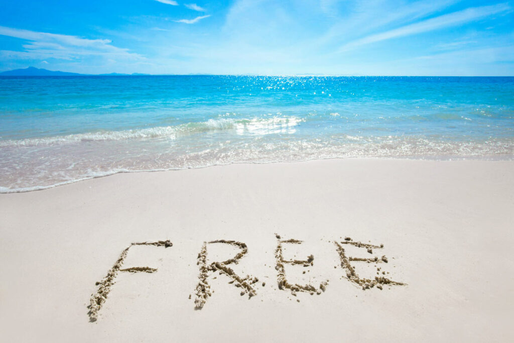 "Sandy beach with blue skies and the word ""FREE' etched into the sand"