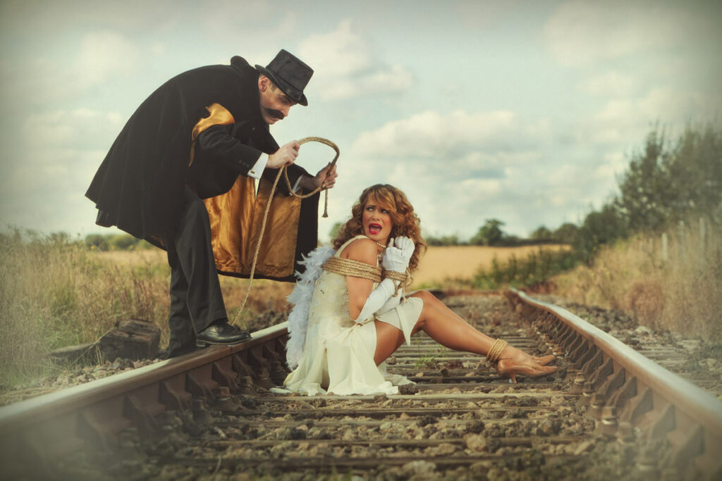 An old fashioned villain with top hat and moustache preparing to tie a woman to the railroad tracks.
