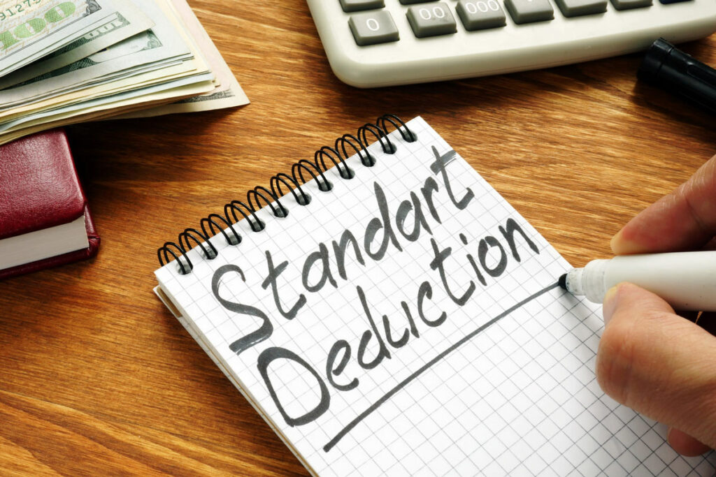 An independent contractor deciding between standard or itemized deductions misspells it as Standart, writing on a table next to calculator and stack of money.