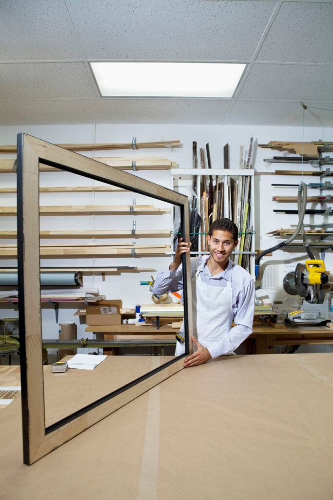 Big picture concept illustrated by frame maker holding up large picture frame in his shop.