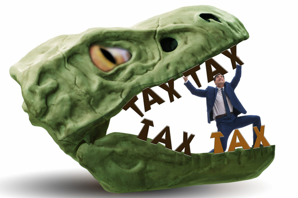 In the jaws of high taxes concept of a Dasher in a suit trapped in jaws of dinosaur head with teeth shaped like the word Tax.