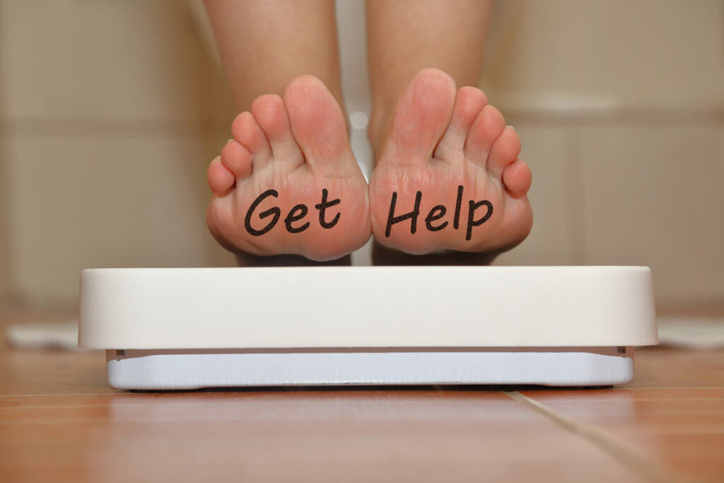 feet on a bathroom scale with hand drawn Get Help text.