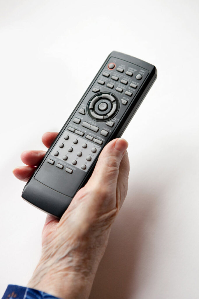 Hand holding on to a remote control.