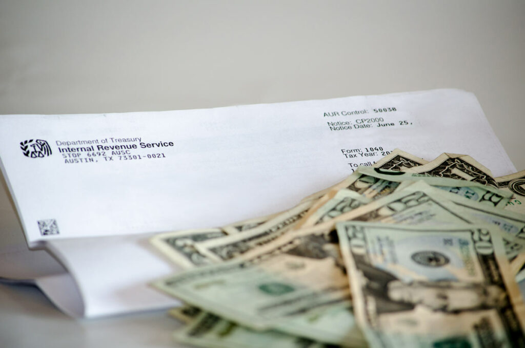 Stack of money next to a notice form from the Internal Revenue Service