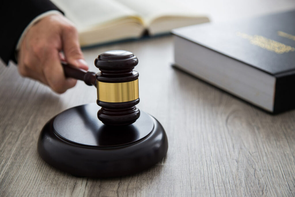 A judge's hand slamming down a gavel preparing to enter a verdict.
