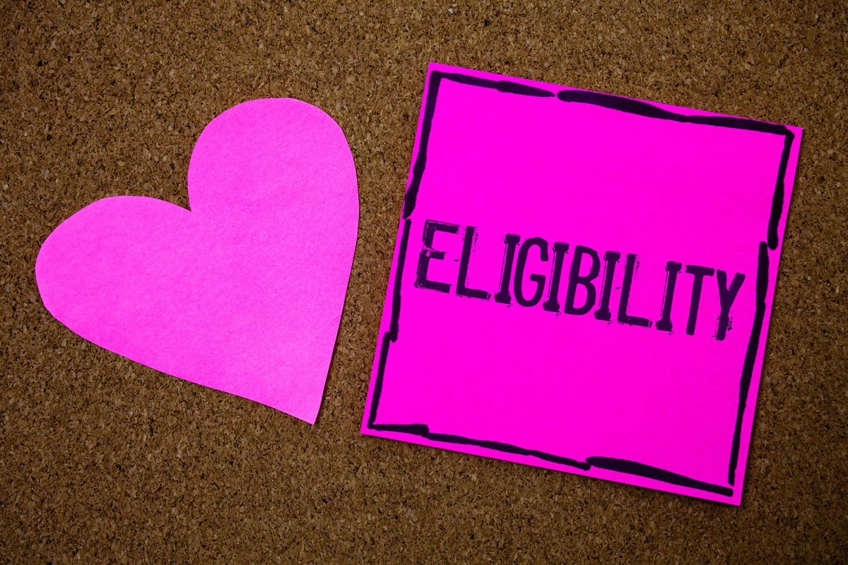 Pink heart cutout and post it note with Eligibility written on it.