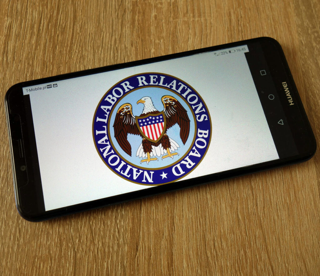 Smart phone on a desk, with the National Labor Relations Board log displaying.