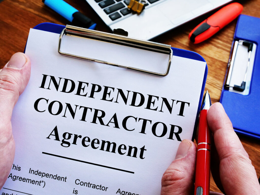 Man with a pen getting ready to sign an Independent Contractor Agreement.
