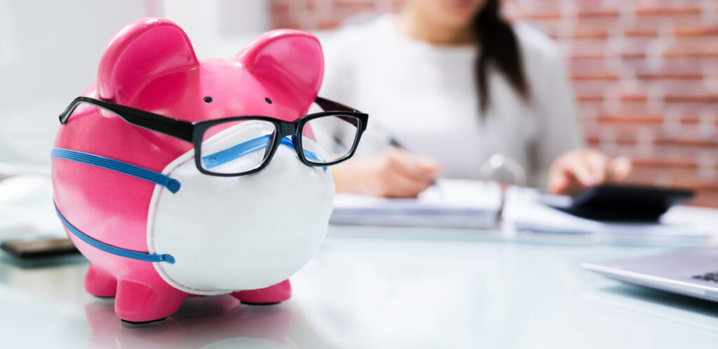 Woman working on her taxes in background with a pink biggy bank wearing a mask and glasses symbolizing smart saving for taxes.