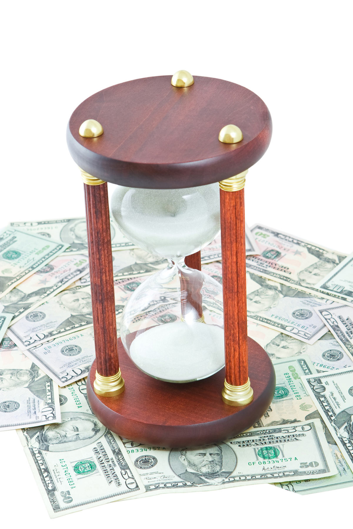 Time is money concept with fancy hourglass on top of a pile of $50 bills.